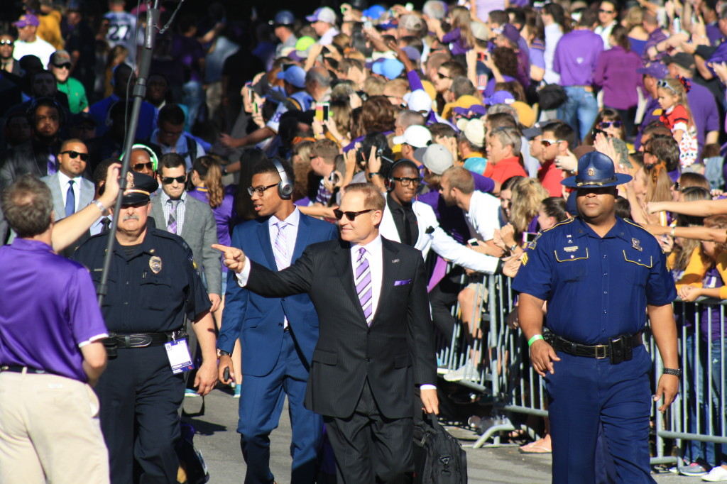 Coach Miles walking down to Tiger Stadium with the team.